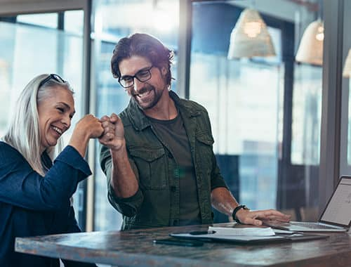 A happy executive woman fist bumps her managed IT service support technician for solving an IT-related issue with excel on her laptop. The business casual dressed IT manager is smiling and happy to have completed a job well done for his client.