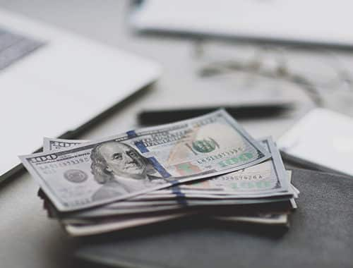 Several thousands of dollars in crisp 100 dollar bills are stacked near a laptop to represent the significant cost savings a business who saved over 91 thousand in the first year after of their managed IT services agreement with IT Support Guys.