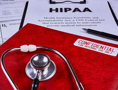 An angled photographo of various HIPAA and security requirement documents.