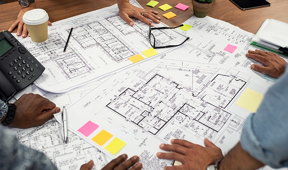 A team of managed IT professionals review an office architectural blue print to identify the best layout of information technology systems.